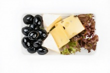 Cheese plate with salad and black olives