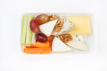 Cheese plate with vegetables, nuts and grape